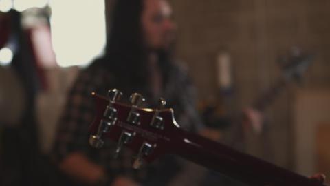 Handheld closeup A bassist and a guitar head Footage