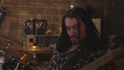 Pan shot of a rock band rehearsing Footage