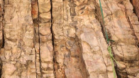 Tilt shot of a rock-climber pulling up his partner's rope Live Action