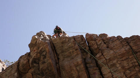 Tilt shot of a rock-climber beginning his descent from the top of a cliff Live Action