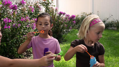 Tracking shot of little girls blowing bubbles Footage