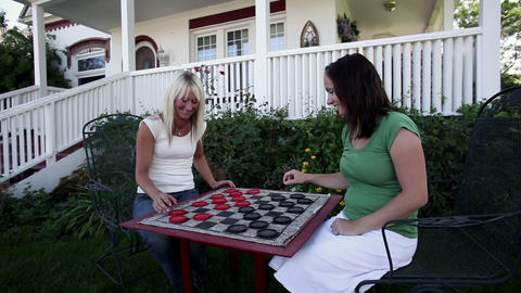 Tracking shot of two women playing checkers Footage