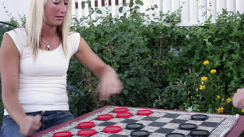 Static shot of two women playing checkers outside Footage