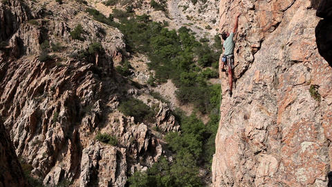 Handheld shot of a rock-climber far from ground Live Action