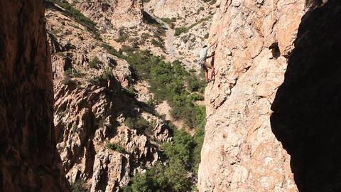 Handheld shot of a rock-climber descending a cliff Live Action