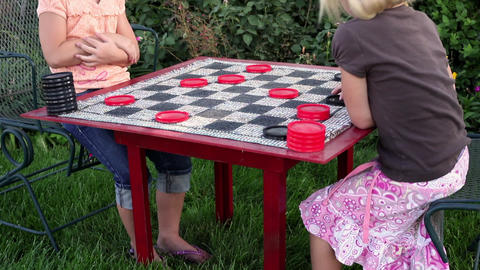 Tilt shot of two little girls playing checkers Footage