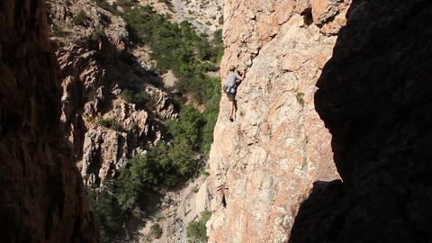 Handheld shot of rock-climber slowly maneuvering up a vertical formation Live Action