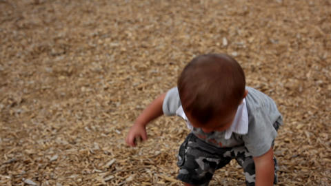 Handheld shot of a Latino toddler throwing leaves Footage