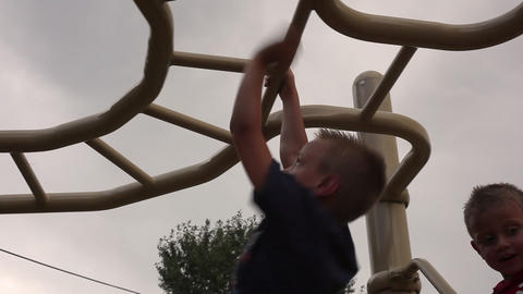 Tracking shot of a small boy hanging from monkey bars Footage