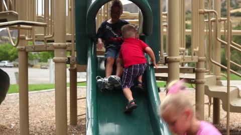 Handheld shot of a little boy climbing up a slide Footage