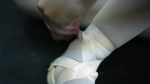 Closeup of a woman tightly tying her toe shoes with pink ribbons Footage