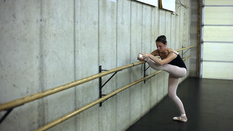 Tracking shot of of a ballet dancer stretching her leg on the barre Footage