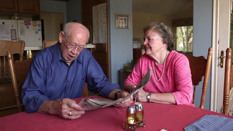 A shot of an elderly couple reading the newspaper together at a beautiful table Footage
