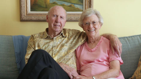 A static shot of a happy elderly couple sitting close to each other on a grey co Footage