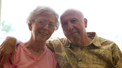 A static shot of an elderly man putting his arm around an elderly woman Footage
