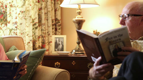 A tracking shot of an elderly couple reading books Footage