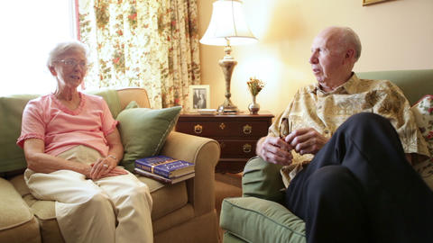 A static shot of an elderly couple conversing with each other in a room Footage
