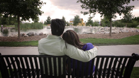 A tracking shot of the back of a couple sitting on a bench gazing off into the d Footage