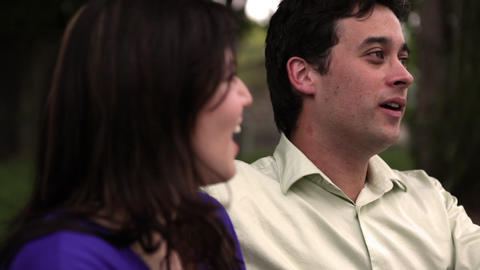A static close up shot of a young couple laughing and joking together on a park  Footage