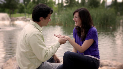 A static shot of a woman looking gleeful as she shows a ring on her finger to he Footage