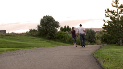 A static shot of a couple walking down a paved path through a park while holding Footage