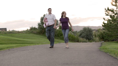 A tracking shot of a couple walking through a park while the father holds a baby Footage
