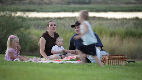 A static close up shot of a family of six having a picnic by a lake at sunset Footage