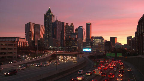 Static, wide, timelapse shot of the Atlanta Skyline with traffic below as the su Footage