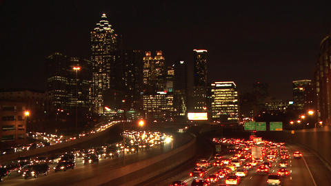 Wide, static, timelapse shot of traffic flowing below the lit up Atlanta Skyline Footage
