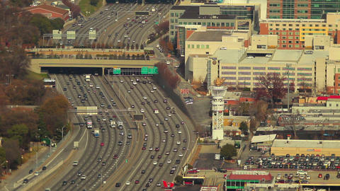 A static, wide shot of flowing cars on the freeway with city buildings on the si Footage