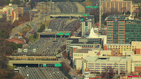 A static, wide shot of flowing cars on the freeway with many city buildings seen Footage