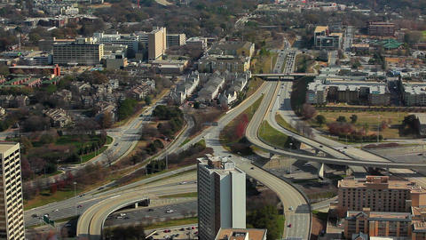 A static, wide shot of cars flowing on the freeway under bridges with buildings  Footage