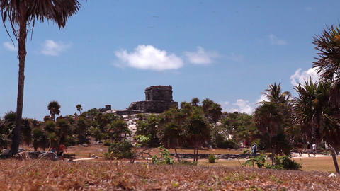 Medium wide, static shot of an ancient building with palm trees and people Footage