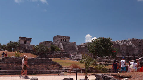 Medium wide, static shot of an ancient building with stairs, trees, and people Footage