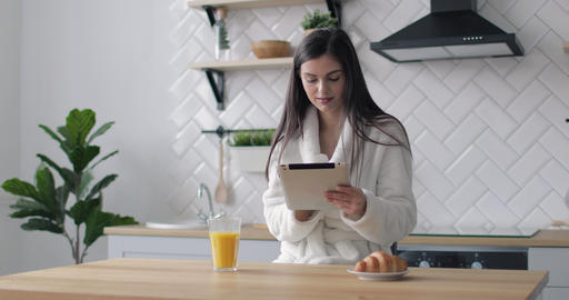Happy Girl using Tablet in Kitchen Live Action