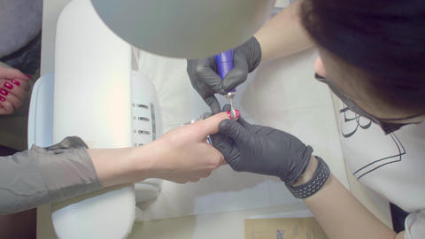 The manicurist removes the old shellac from the client's nail Live Action
