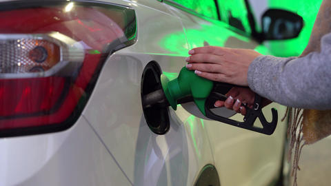 Woman fills petrol into her car at a gas station closeup Live Action