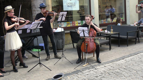 Vilnius, Lithuania – May 2017: street music day. Two young girls and boy play with classical Footage