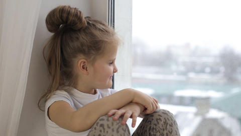 Little girl sitting by the window with a smile and looks out the window Footage