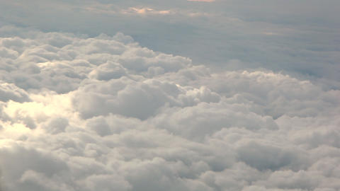 A panning shot of the top of white, fluffy clouds Footage