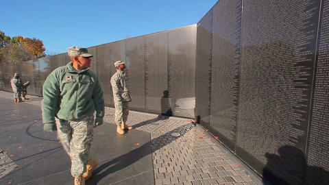 A static shot of soldiers walking past a wall of names of deceased soldiers in W Footage
