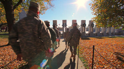 A static shot with a lens flare of soldiers walking towards the World War II Mem Footage