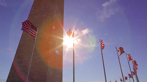 A static shot with a lens flare of flags blowing in front of the Washington Monu Footage