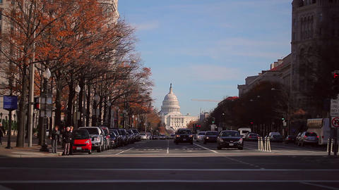 A static shot of a busy road in front of the US Capitol building during the dayt Footage