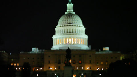 A static shot of the US Capitol with the statue in front of it at night Footage