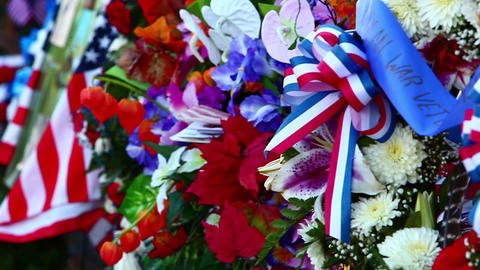Close-up panning shot of flowers and flags at the Korean War Veterans Memorial i Footage