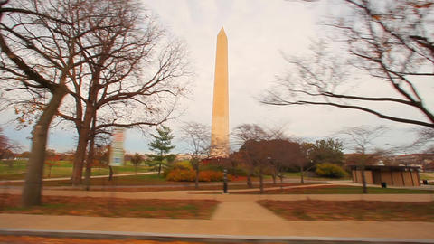 Slow tracking shot of the Washington Monument with trees in foreground Footage