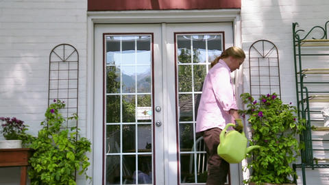 Dolly shot of woman watering plants next to house Footage