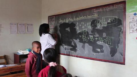 Teacher erasing chalkboard in classroom Footage