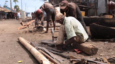 Moving shot of men working in a rundown village Footage
